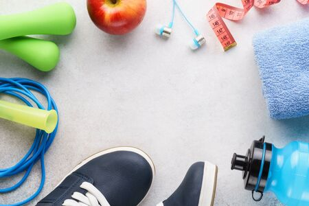 Fitness background with sneakers, water bottle, dumbbells, towel and skipping rope. Sport equipment. Healthy lifestyle concept. Copy space.