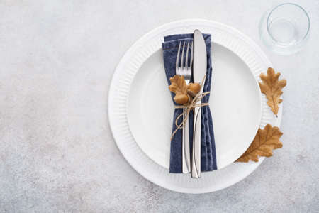 Fall season table setting with white plates and decorated cutlery - fork and knife. Copy space. Flat lay.
