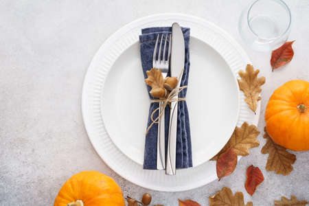 Thanksgiving Day table setting with white plates, decorated cutlery, leaves and pumpkins. Seasonal catering concept. Copy space.