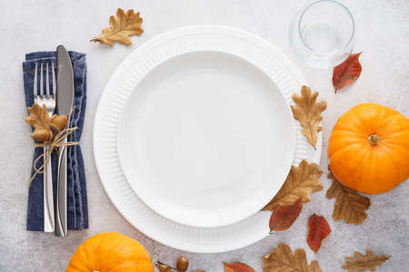 Fall season table setting with pumpkins, leaves and cutlery - fork and knife. White empty plate and decoration around. Copy space. Overhead shot. Zdjęcie Seryjne