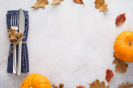 Fall season background with decorated cutlery, leaves and pumpkins. Thanksgiving Day menu concept with copy space. Imagens