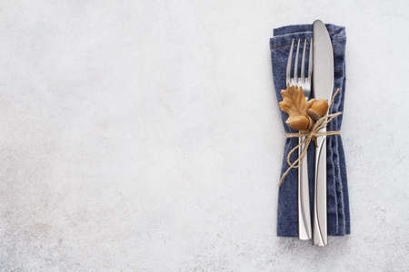 Cutlery - fork and knife and a blue napkin on a light gray background. Fall season decoration. Copy space.