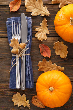 Decorated cutlery - fork and knife on a blue napkin with leaves and pumpkins around.
