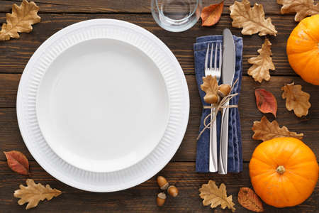 Fall season table setting with pumpkins, leaves and cutlery - fork and knife. White empty plate and decoration around. Copy space. Overhead shot.