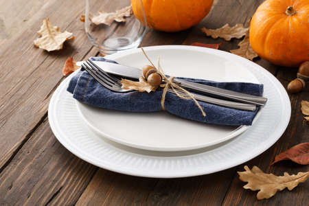 Fall season table setting with leaves and pumpkins. White plates and decorated cutlery on a wooden table. Imagens