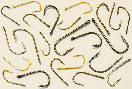 Scattered fishing hooks different size and color on a white background.