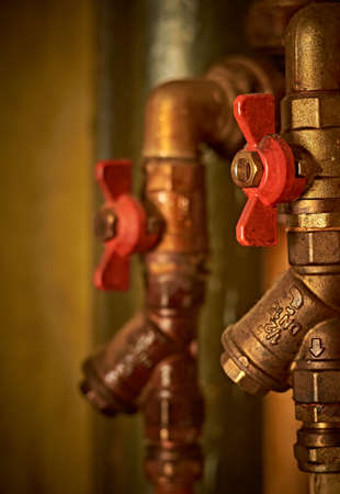 Old water pipes, hot and cold water, with red valves. Vertical orientation. Close up. Banco de Imagens
