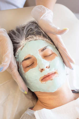 Doctor beautician applied a face mask to a beautiful young woman. Cosmetology skin care, beauty Stock fotó - 131699631