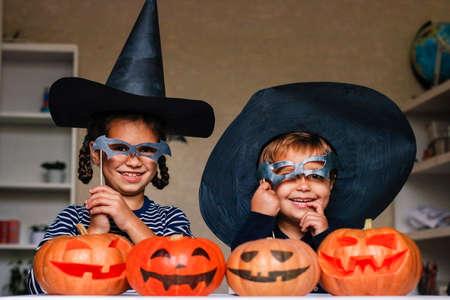 Feliz hermano y hermana celebran Halloween. Niños divertidos en disfraces de carnaval en el interior en la mesa con calabazas. Los niños alegres juegan con calabazas y máscaras en palos. Foto de archivo