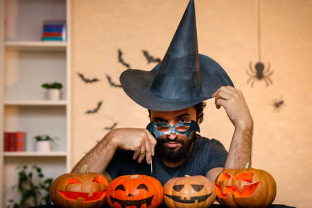 Man, father celebrate Halloween. Cheerful children in carnival costumes indoors. Cheerful children and parents play with pumpkins and black witch hats. Stock fotó