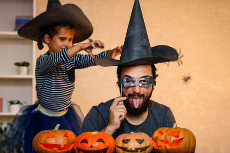 Happy family: father and daughter celebrate Halloween. Cheerful children in carnival costumes indoors at the table with pumpkins. Cheerful child and parents play with pumpkins and black witch hats..