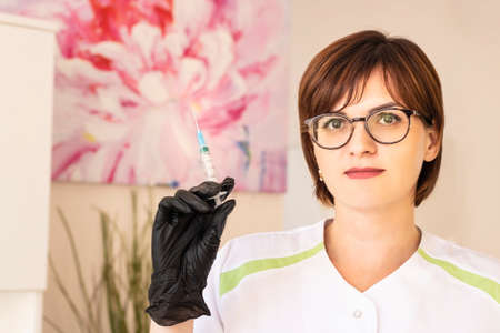 Cosmetologist holds syringe with rejuvenating injections for the face to perform the procedure of removing wrinkles on the skin. Stock fotó