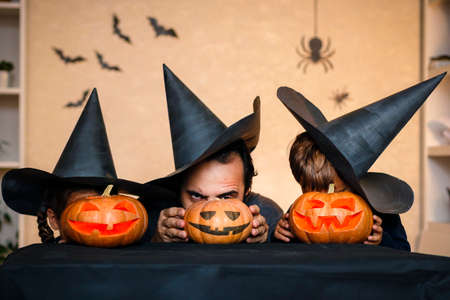 Happy family: father, brother and sister celebrate Halloween. Cheerful children in carnival costumes indoors. Cheerful children and parents play with pumpkins and black witch hats.