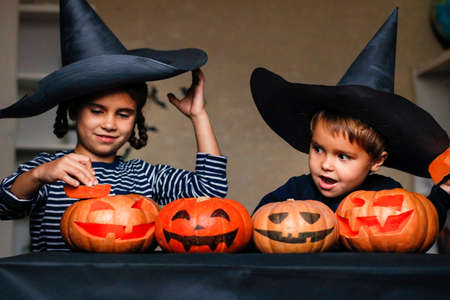 Happy brother and sister celebrate Halloween. Funny children in carnival costumes indoors at the table with pumpkins. Cheerful children play with pumpkins and masks on sticks.