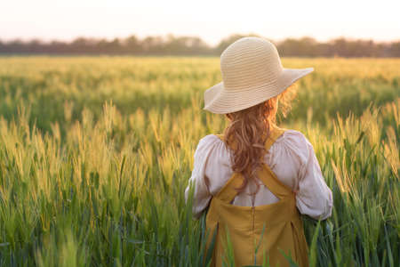 The child is a farmers daughter, a blonde curly-haired girl in a straw hat in a wheat field at sunset. Beautiful, romantic scene. The concept of organic farming