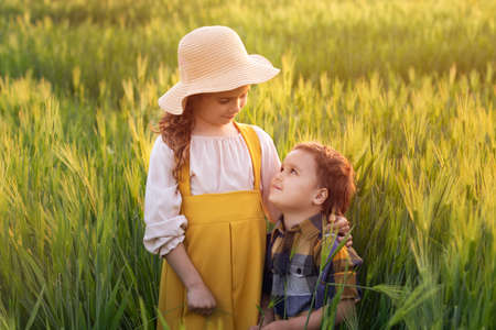 Happy family, brother and sister blonde curly girl in straw hat in wheat field at sunset. Beautiful, romantic scene. The concept of organic farming and healthy lifestyle, healthy food, joy, happiness
