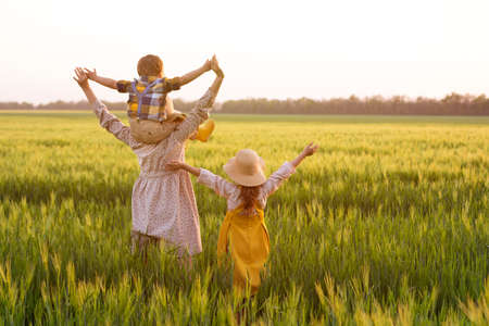 Happy family, mom, son and girl in straw hat in wheat field at sunset. The concept of organic farming and healthy lifestyle, healthy food, happiness and joy Stock fotó