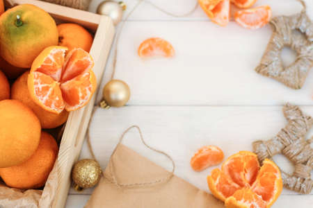 composition with tangerines (oranges, Clementines, citrus) on a white wooden background. Cones, Christmas toys, box of mandarins doing the festive mood, the space for copy. Stock fotó