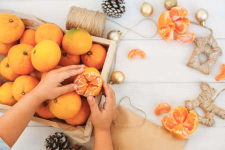 Hands hold, clean tangerine, decorate Christmas toys, a box of tangerines make a festive mood, space to copy.