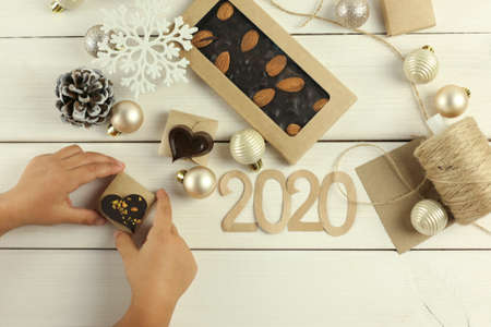 Christmas composition with a chocolate bar on a white wooden background with Christmas toys, balls, cones, snowflakes Stock fotó