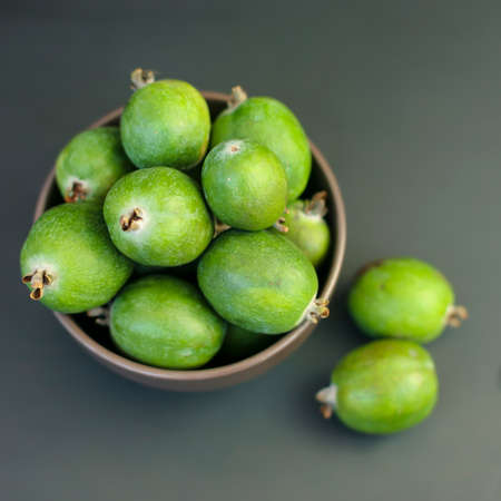 Feijoa green on black background. Feijoa Sellova is a fruit crop from tropical regions. Organic agricultural fruit, healthy food concept, eco-friendly natural products, vegetarian, raw products.
