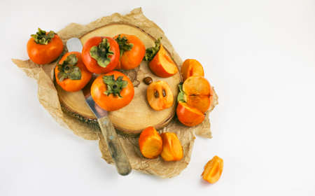 Persimmon lies on a wooden Board on a white background. Persimmon close - up whole and cut into slices with a knife. Organic farming, healthy food concept, eco-friendly products, vegetarian, raw