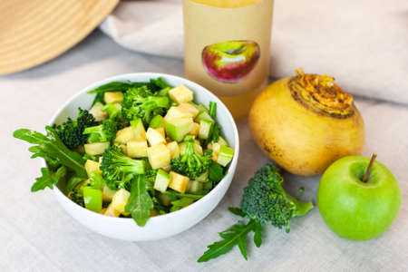 Fresh spring green vegetable salad on a table with apples, turnips, arugula, broccoli on a light background. Farm organic product, home-made.