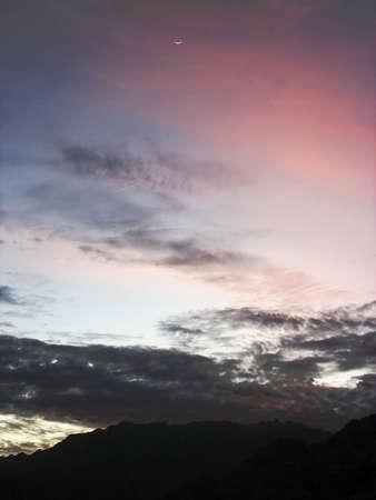 A quarter moon rising in the desert