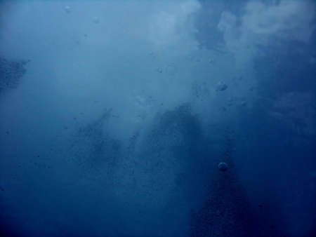 An underwater photo of bubbles and the clouds taken from the sea.
