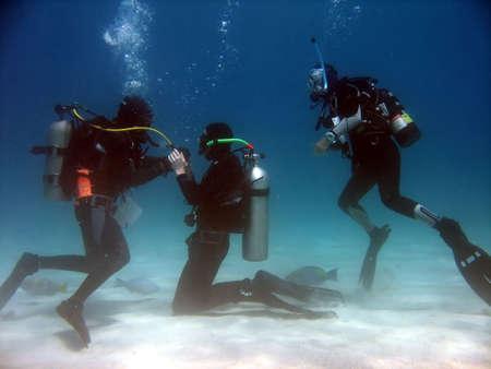 Een scuba student oefenen rekening lucht uit de instructeur terwijl een andere student horloges. Stockfoto