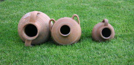 Three earthen potteries onto green grass.