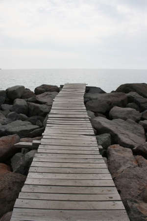 A wooden jetty on the huge stones where Aegean Sea.