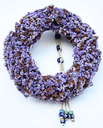 door leaf: Wreath made from natural purple flowers and evil eyes Stock Photo
