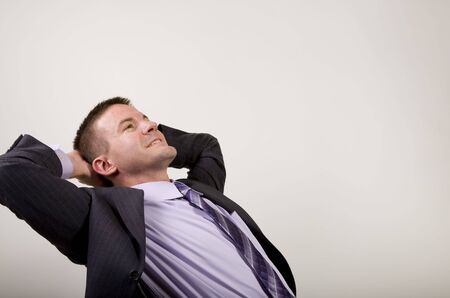 Business man reclines in his chair suggesting daydreaming, relaxation, thinking, planning, etc.