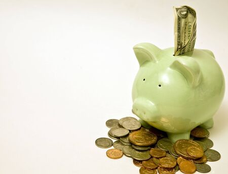 Piggy bank stuffed with money and surrounded by coins. Stock Photo