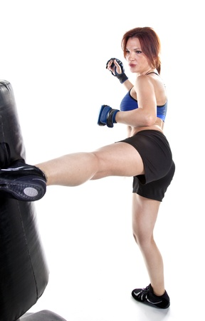 Tough woman kickboxer practicing boxing with a punching bag. Stock Photo