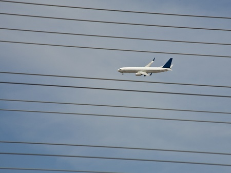 Airliner in Flight and Power Lines Stock Photo