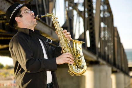 A saxophonist plays outdoors Stock Photo