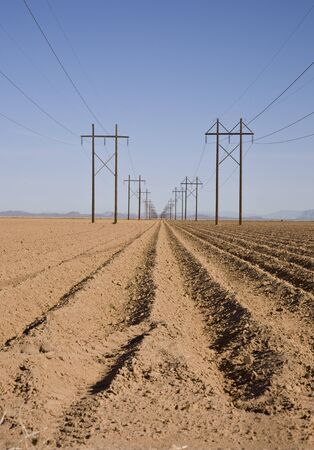 Plowed farm field with two high-tension power lines