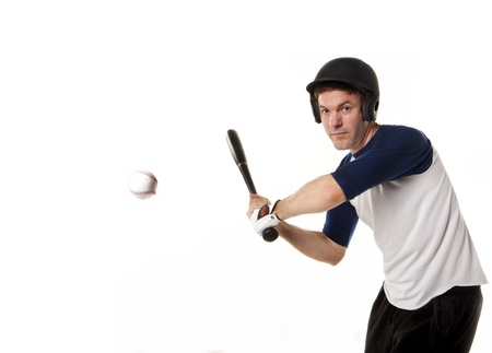 Baseball or softball player at bat hitting a ball and isolated on white
