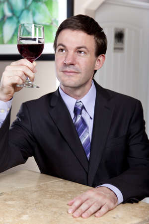 A man  possibly a sommelier  judging the color and clarity of a glass of wine