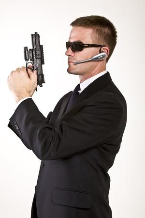 guardia de seguridad: Hombre joven que sugiere un agente de servicio secreto oa un polic�a secreto armado con una pistola