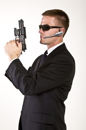 Young man suggesting a secret service agent or secret policeman with armed a gun  photo