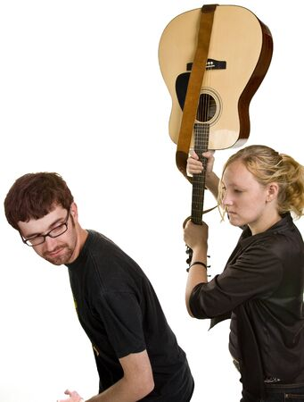 Angry young female musician tries to hit a young man over the head with a guitar.