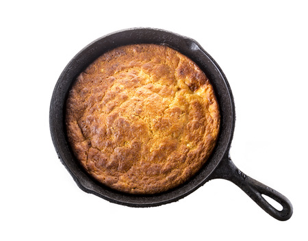 Home Style corn bread in a cast-iron skillet isolated on white.