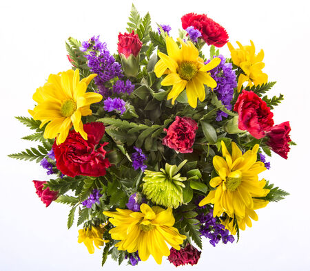 Bouquet of colorful spring flowers isolated on white featuring yellow daisies, red carnations and purple violets.