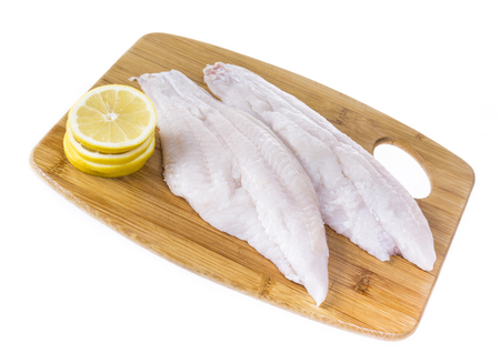 Fresh catfish fillets on a cutting board with lemon and isolated on white. Imagens