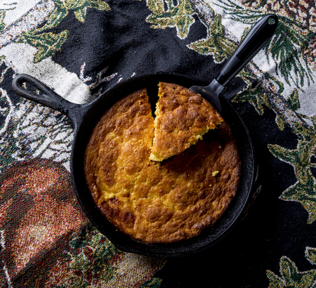 Home Style corn bread being served from a cast-iron skillet.