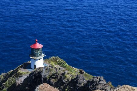 Makapuu lighthouse on a cliff in Oahu Hawaii over the beautiful blue Pacific ocean.