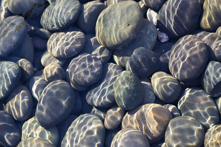 river stones: Multicolored pebbles and cobblestones in a stream with sunlight diffraction patterns from surface ripples useful as a background or a texture. Stock Photo